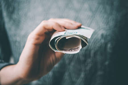destitution: Hands holding rolled russian rouble bills. Selective focus. Toned picture Stock Photo