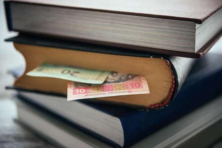 Pile of books and ukrainian hryvnia bills Stock Photo