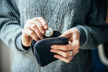 Hände halten britische Pfund-Münze und kleinen Geldbeutel