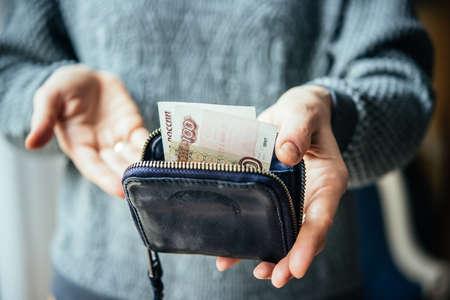 Hände halten russische Rubel Rechnungen und kleine Geldbeutel