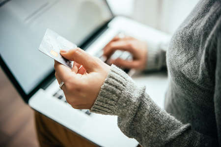 Hands holding plastic credit card and using laptop. Online shopping concept