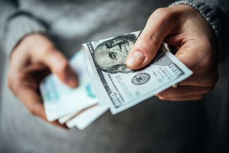 devaluation: Hands holding russian rouble and us dollar bills