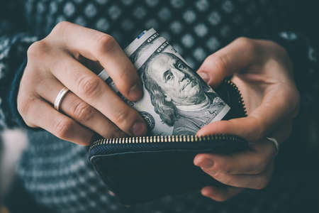 Hands holding us dollar bills and small money pouch. Toned picture Foto de archivo