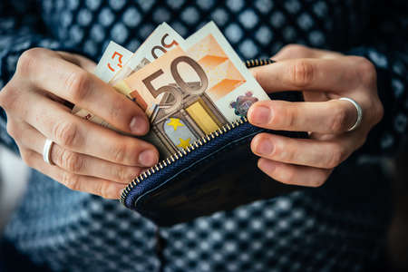 Hands holding euro bills and small money pouch