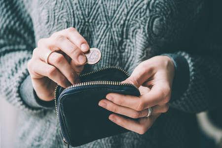 pieniądze: Trzymając się za ręce monety jednego euro i małą torebkę pieniędzy. stonowanych obraz Zdjęcie Seryjne