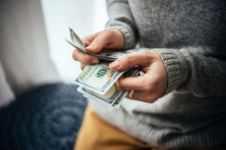 destitution: Hands counting us dollar bills