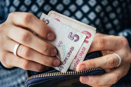 destitution: Hands holding turkish lira bills and small money pouch