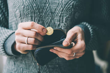 Hands holding russian rouble coin and small money pouch. Toned picture