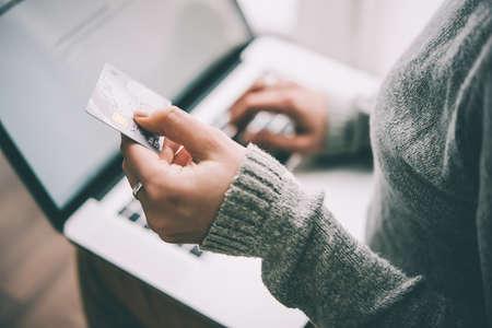 tarjeta de credito: Manos que sostienen la tarjeta de crédito de plástico y usando la computadora portátil. el concepto de compra en línea. cuadro entonado Foto de archivo