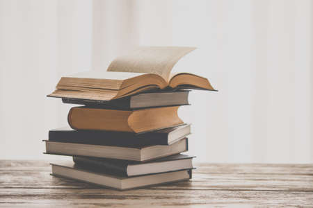 Pile of books on wooden table. Education and reading concept. Toned picture