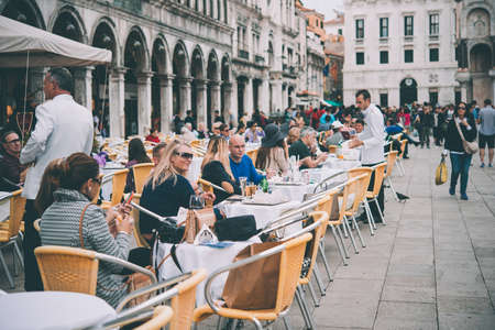 historical: VENICE, ITALY - OCTOBER 12, 2015: Tourists are sitting in one of the cafes at San Marco square in Venice, Italy. Toned picture
