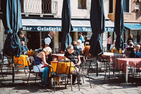 personas sentadas: VENICE, ITALY - OCTOBER 11: People are sitting at the outside terrace of a small cafe in Venice, Italy