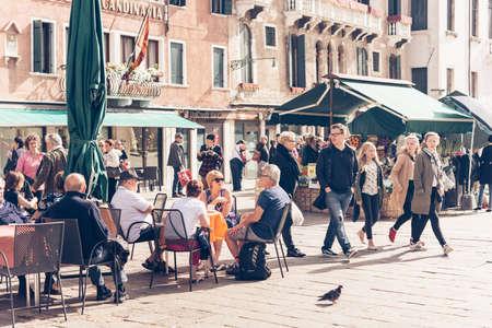 사람들: 베니스, 이탈리아 - 10 월 11 일 : 사람들이 베니스, 이탈리아에서 작은 카페의 야외 테라스에 앉아있다. 톤의 그림 에디토리얼