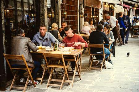 personas en la calle: VENECIA, Italia - 11 de octubre: La gente está sentada en la terraza exterior de un pequeño café en Venecia, Italia Editorial