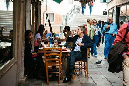 gente sentada: VENECIA, Italia - 11 de octubre: La gente está sentada en la terraza exterior de un pequeño café en Venecia, Italia Editorial