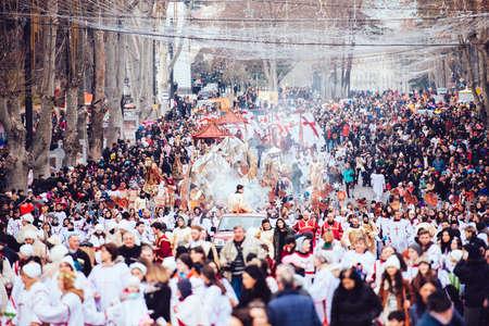rustaveli: GEORGIA, TBILISI - JANUARY 7, 2016:  Participants march during Alilo, a religious procession to celebrate Orthodox Christmas in center of Tbilisi, Georgia, Caucasus region. Toned in old film style