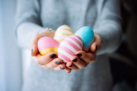 Hands holding modern painted easter eggs Stock Photo