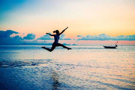 'koh samui': A beautiful young woman jumps over the sea at sunset at Koh Samui, Thailand. Selective focus