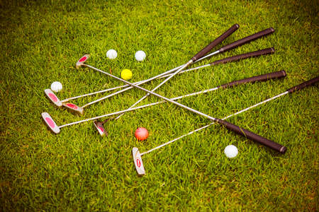 mini: Mini golf putters and balls on the grass at mini golf club. Toned picture Stock Photo