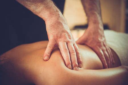 masoterapia: Mujer que goza de relajante masaje de espalda en el centro de spa cosmetología. tratamientos de belleza, cuidado del cuerpo, cuidado de la piel, salud, bienestar concepto. cuadro entonado Foto de archivo