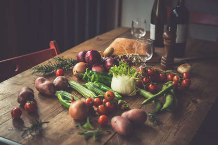 Different fresh farm vegetables on wooden table. Wine bottles and bread on background. Autumn harvest and healthy organic food concept. Toned picture