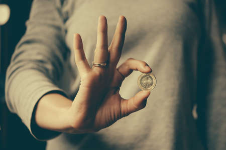 Hands holding turkish lira coin. Toned image