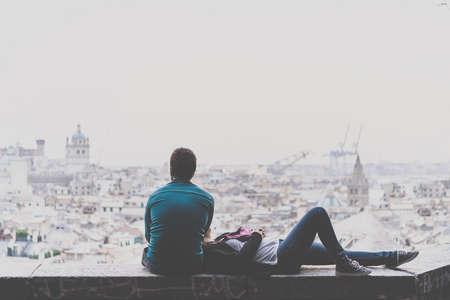 familias jovenes: Pareja joven se está relajando y disfrutando de la vista de la ciudad. cuadro entonado