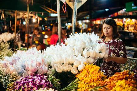 flower seller: BANGKOK, THAILAND - MARCH 4, 2016: Flowers on sale at night flower market in Bangkok, Thailand. Editorial