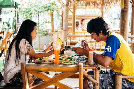 dinners: KOH SAMUI, THAILAND - MARCH 18, 2016: Asian couple enjoys their traditional thai dinners at one of the restaurants at Koh Samui, Thailand. Editorial