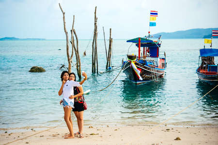 pecheur: Koh Samui, Thaïlande - 18 mars 2016: Les touristes font selfies en face des bateaux de pêche à Koh Samui, en Thaïlande.
