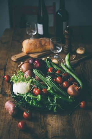 food and wine: Different fresh farm vegetables on wooden table. Wine bottles and bread on background. Autumn harvest and healthy organic food concept. Toned picture