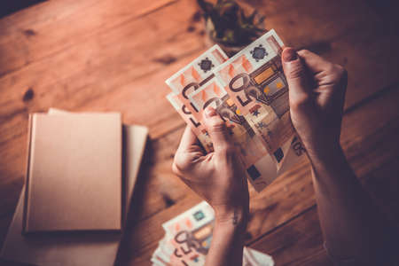 pieniądze: Trzymając się za ręce Europejskiej rachunki euro. stonowanych obraz