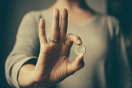 destitution: Hands holding european Euro coin. Toned image Stock Photo