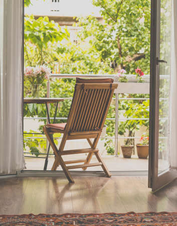 Beautiful terrace or balcony with small table, chair and flowers. Garden view. Toned picture Archivio Fotografico