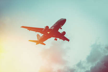 Passenger plane in the sky at sunrise or sunset. Vacation and travel concept. Toned image 스톡 콘텐츠