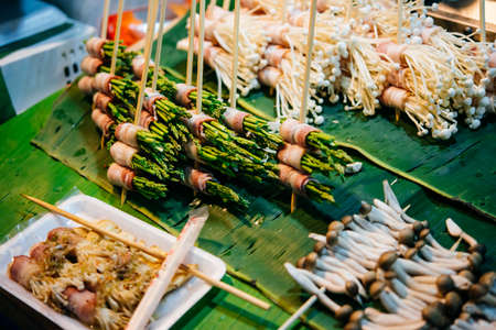 night stick: Grilled asparagus and different mushrooms on sale at street food market in Bangkok, Thailand.