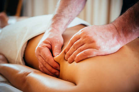 Woman enjoying relaxing back massage in cosmetology spa centre. Beauty treatment, body care, skin care, wellness, wellbeing concept