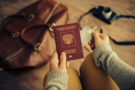 viagem: Pessoa segura russo passaporte de viagem e cartão de crédito plástico nas mãos com bolsa de couro e câmera de foto no fundo. Viagens e conceito de turismo. retrato tonificado