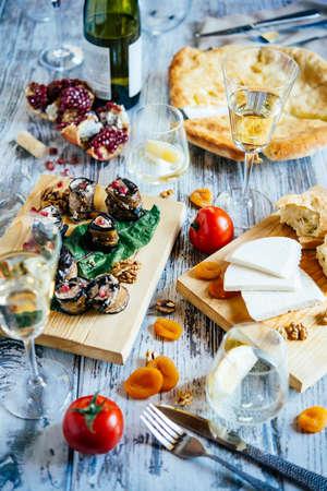 Traditionele Georgische maaltijden van khachapuri, aubergine broodjes, imeretian en suluguni kaas en wijn worden geserveerd voor lunch of diner op houten tafel. Stockfoto