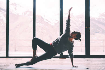 Young beautiful woman practicing yoga with mountain view in the background. Wellness concept. Calmness and relax, woman happiness. Toned picture