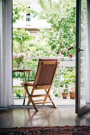 Belle terrasse ou un balcon avec une petite table, une chaise et des fleurs. Vue du jardin