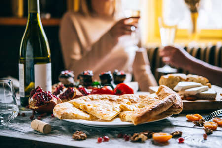 appetizers: People are having traditional georgian lunch or dinner of khachapuri, aubergine rolls, imeretian and suluguni cheeses and wine served on wooden table. Stock Photo