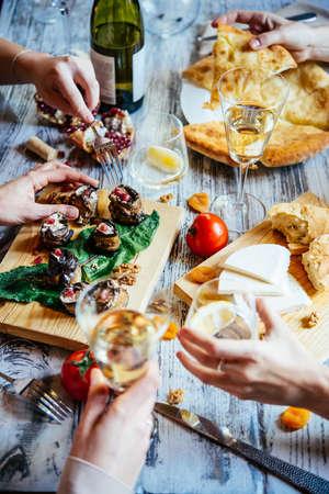 Le persone stanno avendo pranzo tradizionale della Georgia o la cena di khachapuri, involtini di melanzane, formaggi imeretian e Suluguni e vino servito su tavola di legno.