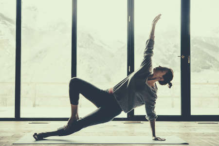 Young beautiful woman practicing yoga with mountain view in the background. Freedom concept. Calmness and relax, woman happiness. Toned picture