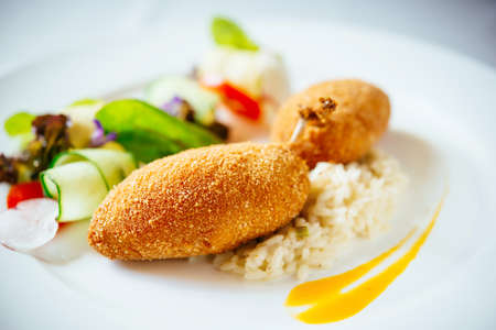 Chicken Kiev with risotto and salad served on a plate