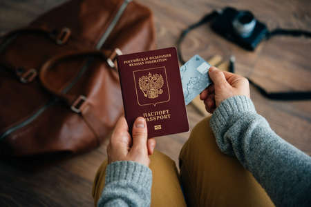 Person holds Russian travel passport and plastic credit card in hands with leather bag and photo camera in the background. Travel and tourism concept.