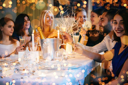 Friends celebrating Christmas or New Year eve. Party table with champagne. 스톡 콘텐츠
