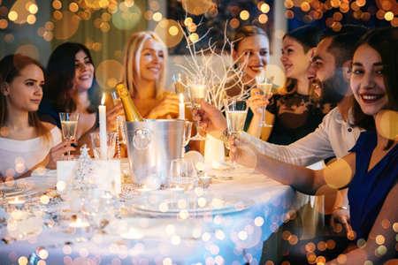 Przyjaciele świętują Boże Narodzenie lub Sylwestra. Stół przyjęć z szampanem.