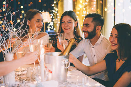 Friends celebrating Christmas or New Year eve. Party table with champagne. Toned picture 版權商用圖片 - 69677419