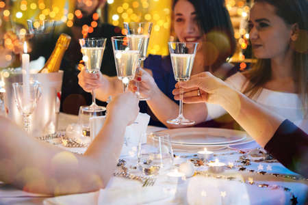 men talking: Friends celebrating Christmas or New Year eve. Party table with champagne. Stock Photo
